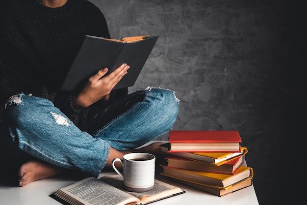 Meisje leest boeken, studeert, ontwikkelt zich met een kopje koffie op een witte tafel en een grijze achtergrond.