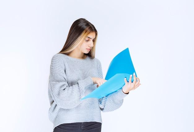 Meisje leest de rapporten over de blauwe map en maakt opmerkingen.