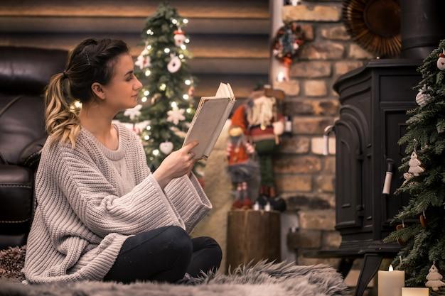 Meisje leest een boek in een gezellige huiselijke sfeer bij de open haard