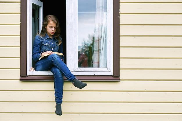 Meisje leest een boek zittend in het raam van een landhuis met haar benen buiten bungelend