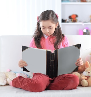 Meisje leest een boek zittend op de bank in de kinderkamer.