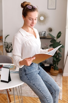 Meisje leest thuis een tijdschrift in de buurt van de werkplek