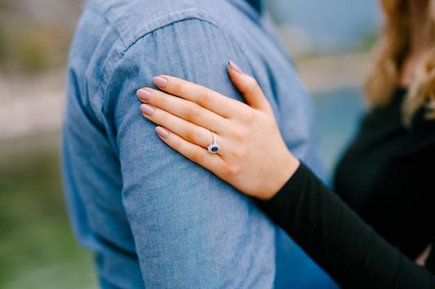 Meisje legde haar hand met een ring op de schouder van de man close-up