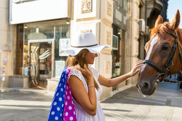 Meisje legt paarden in het centrum van de stad