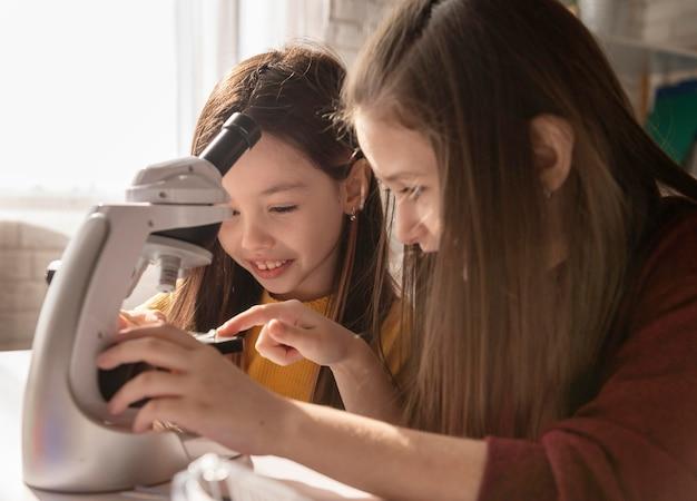 Meisje leren met microscoop close-up