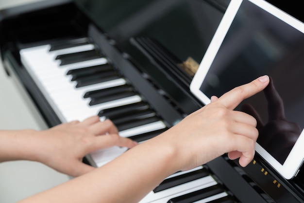 Meisje leren om de piano te spelen met een tablet