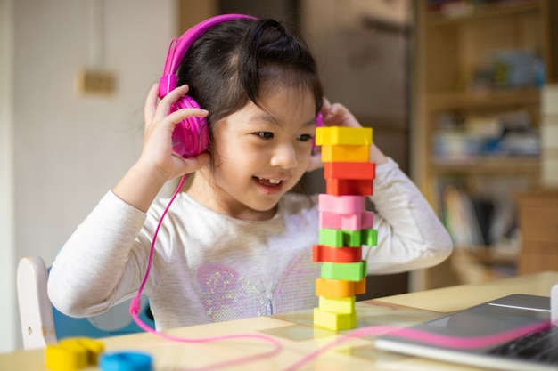 Meisje leren van hoofdtelefoon en laptop