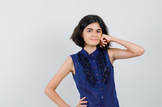 Meisje leunend vuist op wang in blauwe blouse en ziet er prachtig uit