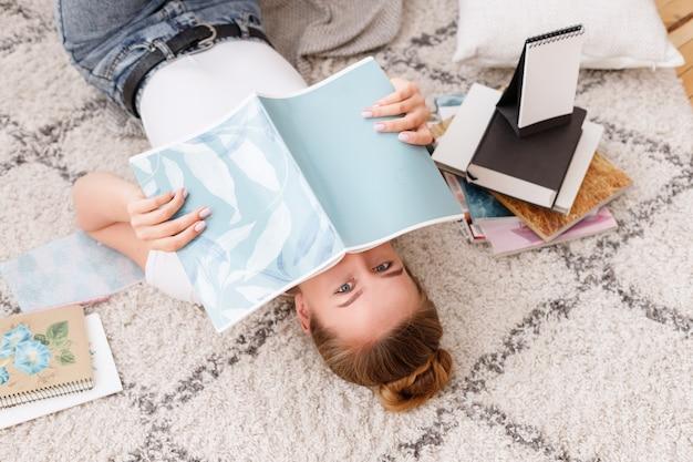 Meisje liegt en bedekt haar gezicht met een notitieboekje