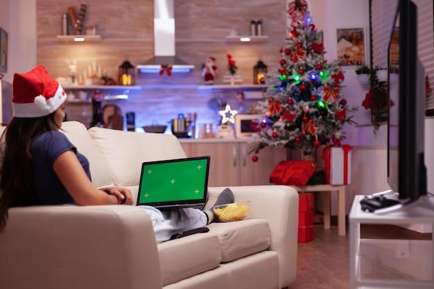 Meisje liggend op de bank met mock-up groen scherm chroma key laptop