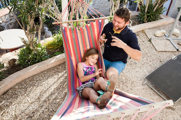 Meisje liggend op de hangmat naast haar vader
