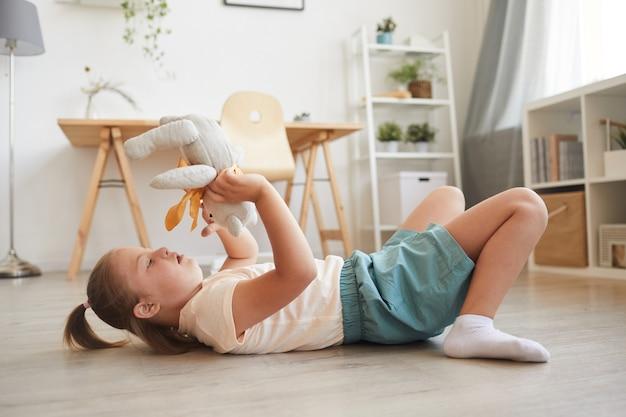 Meisje liggend op de vloer en spelen met haar speelgoed teddybeer in de kamer thuis