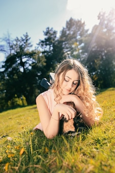 Meisje liggend op gras met kat. lente of zomer warm weer concept.