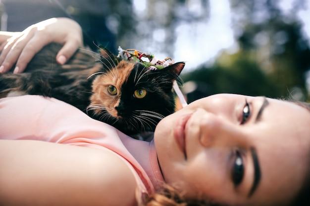 Meisje liggend op gras met kat op borst. lente of zomer warm weer concept.