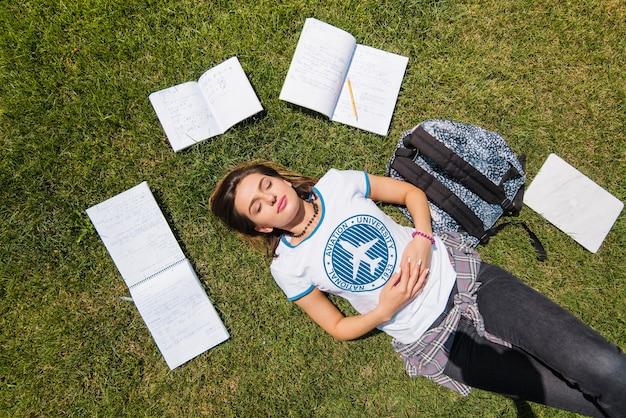 Meisje liggend op gras omringd door notitieblokken