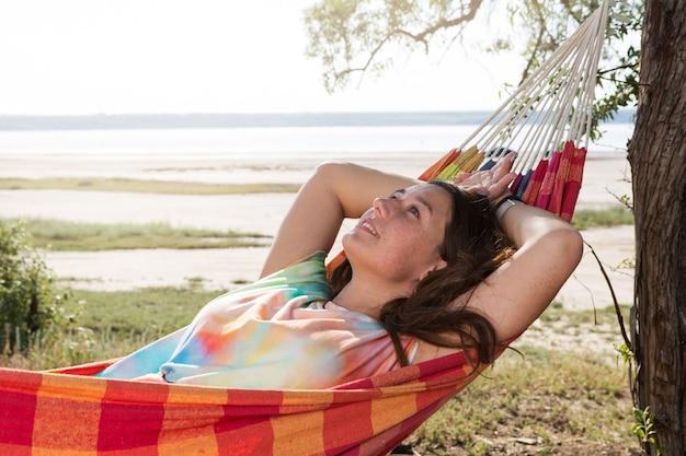 Meisje ligt in een gekleurde hangmat en kijkt dromerig op, tegen de achtergrond van het meer, concept