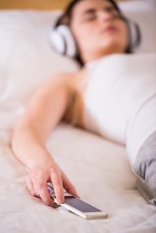 Meisje ligt op het bed in koptelefoon luisteren naar muziek.