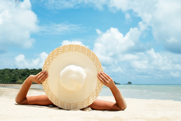 Meisje ligt op het witte zand op het strand