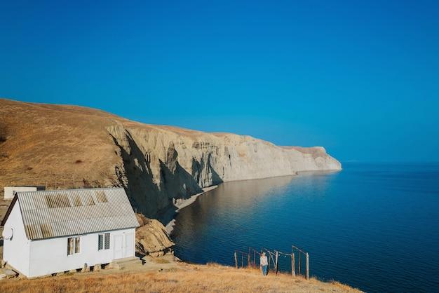 Meisje loopt aan de zeekust op een berghelling in de buurt van het kleine huis
