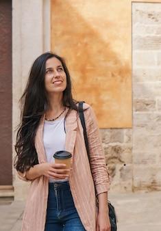 Meisje loopt door een oude stad op vakantie met een koffiekopje