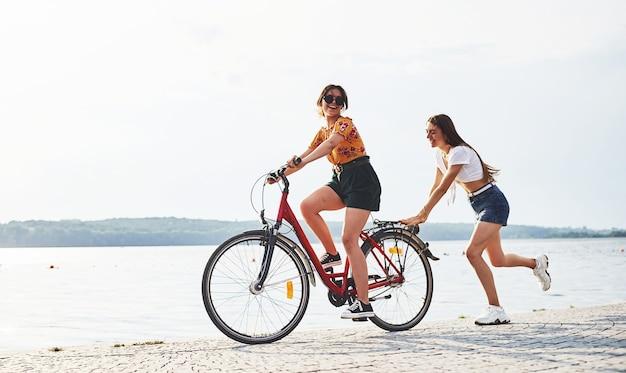 Meisje loopt in de buurt van fiets. twee vriendinnen op de fiets hebben plezier op het strand bij het meer.