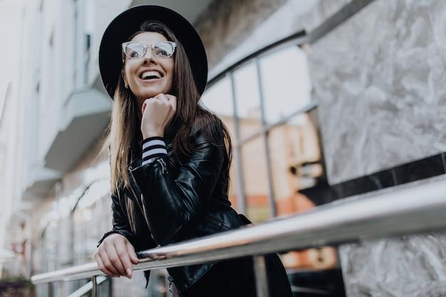 Meisje loopt in de stad na regen in de buurt van schitterende etalages bij koud weer overdag