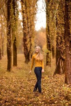Meisje loopt in het herfstbos. een jonge vrouw draait tegen de achtergrond van sinaasappelbomen..