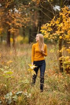 Meisje loopt in het herfstbos. een jonge vrouw op een achtergrond van gele en oranje bladeren