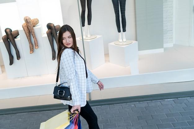 Meisje loopt langs etalages en houdt veelkleurige boodschappentassen vast. succesvol winkelen.