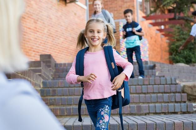Meisje loopt naar haar moeder na school