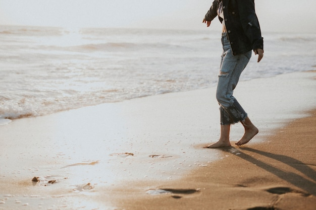 Meisje loopt op blote voeten aan de kust