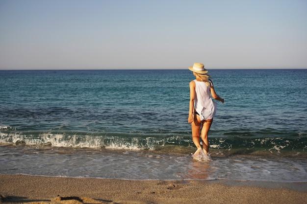 Meisje loopt op strand mooie blonde vrouw in witte blouse en strohoed