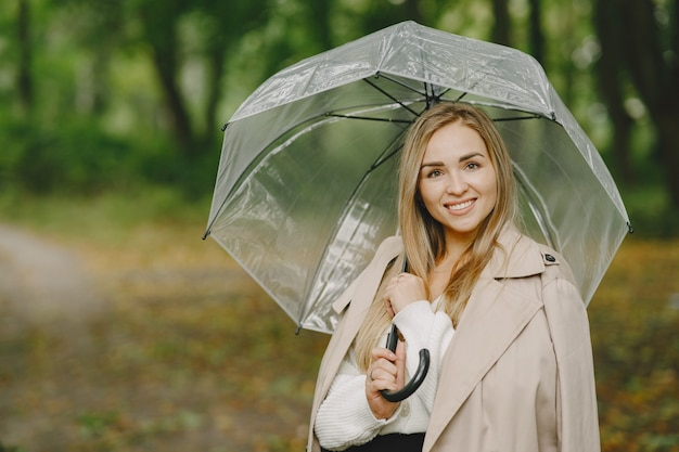 Meisje loopt. vrouw in een bruine jas. blonde met paraplu.