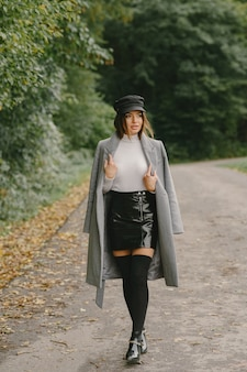 Meisje loopt. vrouw in een grijze jas. brunette met een zwarte pet.