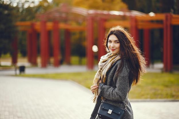 Meisje loopt. vrouw in een jas. brunette met een sjaal.
