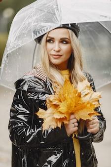 Meisje loopt. vrouw in een zwarte jas. blondje met een zwarte pet. dame met paraplu.