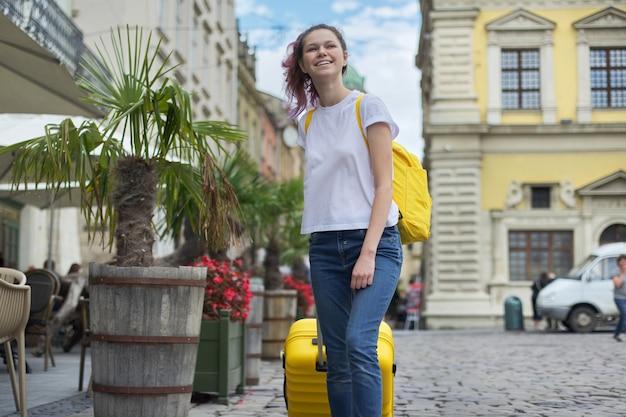 Meisje lopen met rugzak en gele koffer op straat in de stad