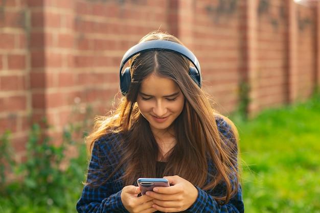 Meisje luisteren naar muziek met koptelefoon op straat, dansen, genieten