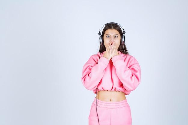 Meisje luistert naar de koptelefoon en vraagt om stilte. hoge kwaliteit foto