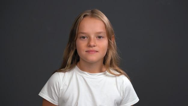 Meisje luistert naar haar ouders kijken naar de voorkant, gekleed in een wit t-shirt en een zwarte broek geïsoleerd op zwarte muur