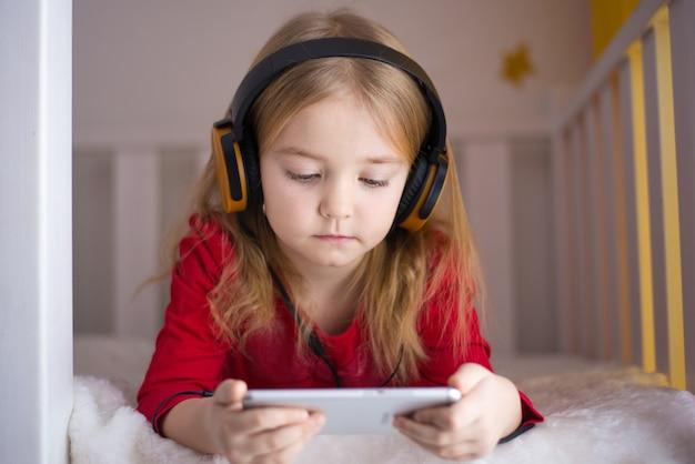Meisje luistert naar kinder audioboek en muziek op haar mobiele telefoon met koptelefoon, ontwikkeling van het kind, moderne technologie