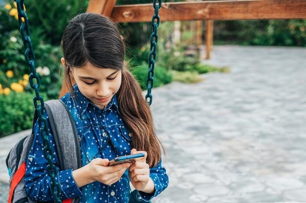 Meisje luistert naar muziek op haar telefoon zittend op een schommel met een rugzak achter haar rug.