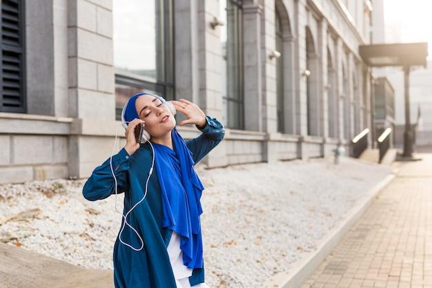 Meisje luistert naar muziek via koptelefoon met kopie ruimte
