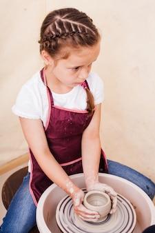 Meisje maakt aardewerk van witte klei op een pottenbakkersschijf