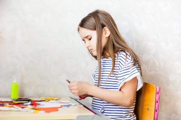 Meisje maakt ambachten, briefkaart, papier, veelkleurig papier voor creativiteit