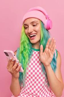 Meisje maakt begroetingsgebaar zwaait hand naar camera en zegt hallo maakt gebruik van draadloze hoofdtelefoons en moderne smartphone geniet van videogesprek met vriend poses op roze