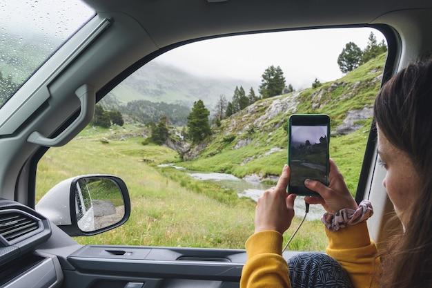 Meisje maakt een foto van een landschap vanuit het raam van een camper