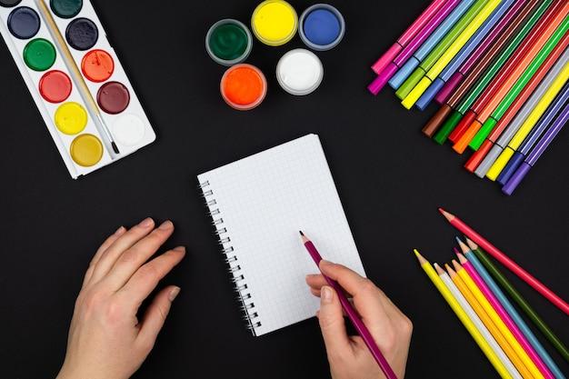 Meisje maakt een notitie in een notitieblok, naast potloden en verf op een zwarte achtergrond