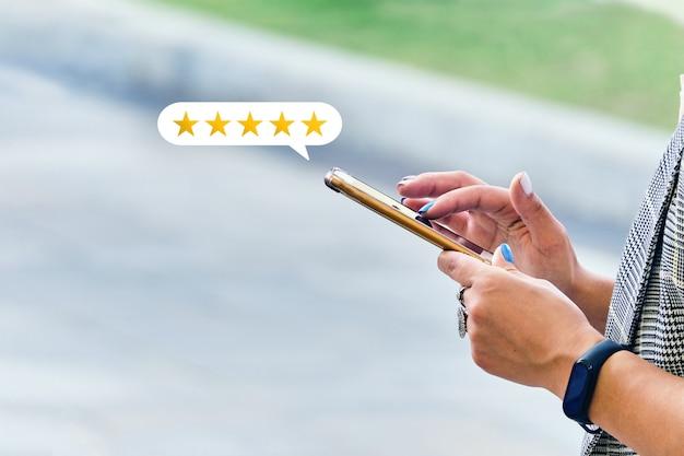 Meisje maakt een recensie met een beoordeling met behulp van een smartphone.