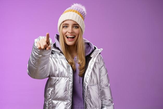 Meisje maakt grapje van onhandige vriend wijzende vinger wreed onwetend lachen om grappige amusante situatie die aangeeft dat camera vrolijk spottend vriendje staat, het dragen van een zilveren winterjasmuts.
